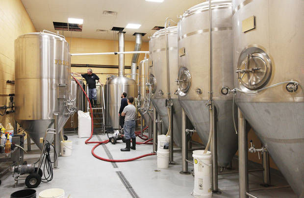 Mustang Brewing Co. brewmaster Gary Shellman, left, prepares the mash tank Wednesday for a brewing session at the OKCity Brewing Cooperative in Oklahoma City. Mustang, like several other Oklahoma brewers, is seeking to ramp up out-of-state beer sales. PHOTOS BY PAUL SOUTHERLAND, THE OKLAHOMAN