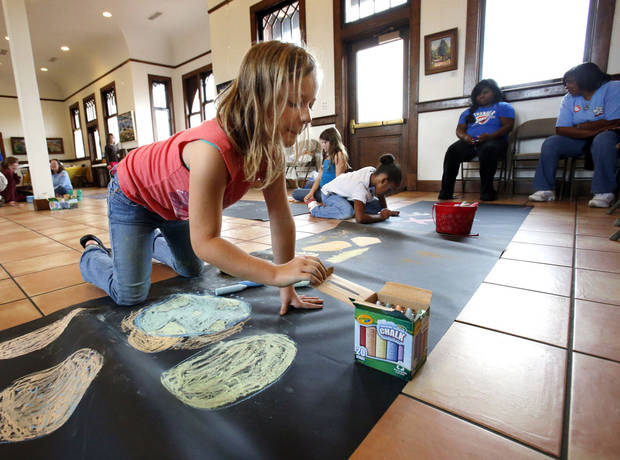 Cetani Lenker, 9, chooses her colors for a chalk art contest at the Santa Fe Depot in Norman. The children�s art contest was held as a prelude to the annual CROP Walk to Stop Hunger. The Norman walk is Sunday.