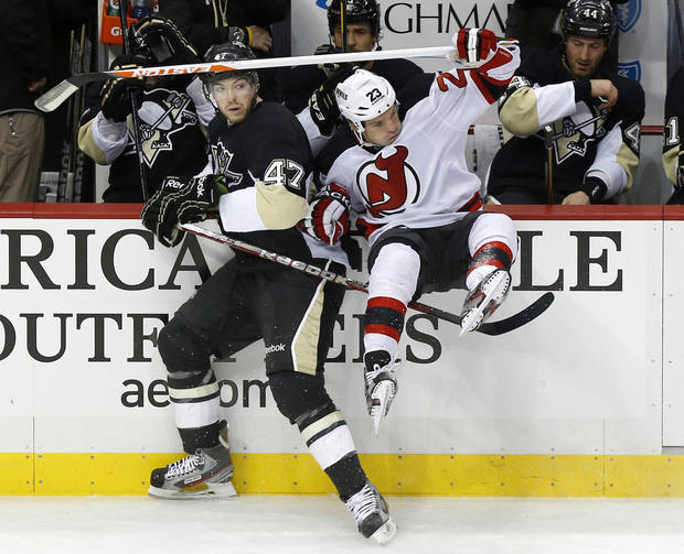 New Jersey Devils' David Clarkson (23) is checked into the bench by Pittsburgh Penguins' Simon Despres (47) during the first period of an NHL hockey game, Saturday, Feb. 2, 2013, in Pittsburgh. (AP Photo/Keith Srakocic)