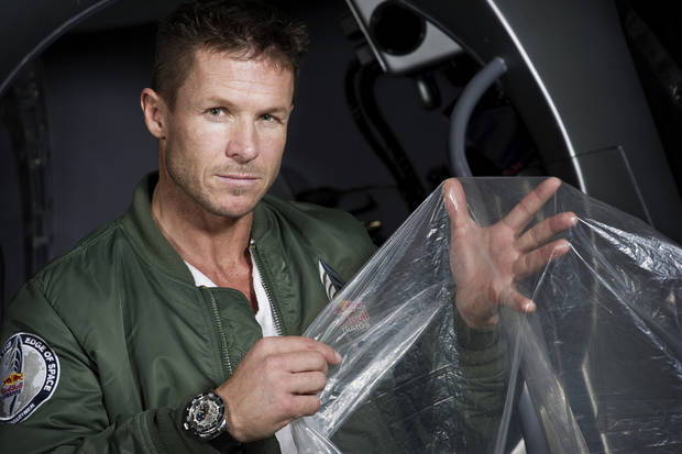 "In this Feb. 23, 2012 photo provided by Red Bull Stratos, pilot Felix Buamgartner of Austria shows a piece of the balloon material during the Red Bull Stratos egress training in Lancaster, Calif. It�s described as a �40-acre dry cleaner bag,� that, when first filled, will stretch 55 stories high. On Monday, this special ultra-thin helium balloon is scheduled to liftoff from Roswell, N.M., to carry ""Fearless Felix"" Baumgartner 23 miles into the stratosphere for what he hopes will be a history-making, sound barrier-breaking skydive. (AP Photo/Red Bull Stratos, Joerg Mitter)"