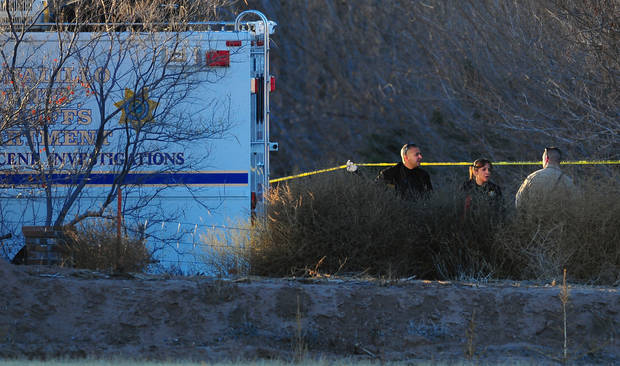 Bernalillo Sheriff Deputies investigate at the scene of the multiple homicide at South Valley in Albuquerque, N.M., on Sunday Jan. 20, 2013. A 15-year-old boy remained in custody Sunday night as detectives tried to piece together what led to the shooting of five people, including three young children, who were found dead in a New Mexico home. (AP Photo/The Albuquerque Journal, Adolphe Pierre-Louis)