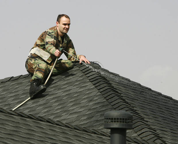 Paul Thurman sits on top of his house keeping it wet with a garden hose as wildfires burn near his home in the Windsong Addition in Midwest City, Okla., Thursday, April 9, 2009.  Photo by Jim Beckel, The Oklahoman