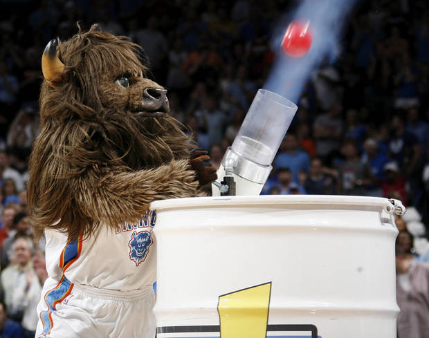 Rumble the Bison fires balls into the crowd during an Oklahoma Lottery promotion during the NBA basketball game between the Miami Heat and the Oklahoma City Thunder at Chesapeake Energy Arena in Oklahoma City, Sunday, March 25, 2012. Photo by Nate Billings, The Oklahoman