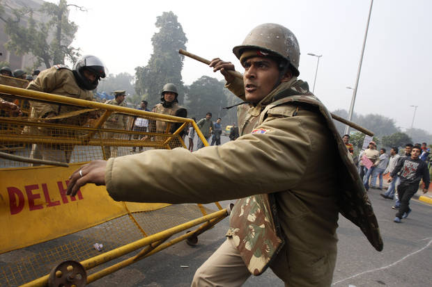 An Indian policeman baton charges to disperse protesters demonstrating against a gang rape and brutal beating of a 23-year-old student on a bus, in New Delhi, India, Sunday, Dec. 23, 2012. The attack last Sunday has sparked days of protests across the country. (AP Photo/Tsering Topgyal)