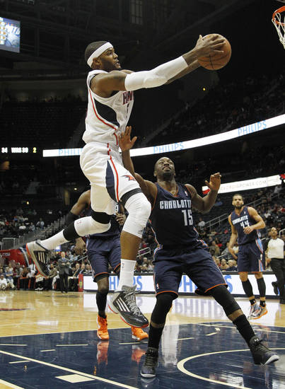 Atlanta Hawks forward Josh Smith (5) goes to the basket as Charlotte Bobcats guard Kemba Walker (15) defends in the first half of an NBA basketball game Wednesday, Nov. 28, 2012 in Atlanta. (AP Photo/John Bazemore)