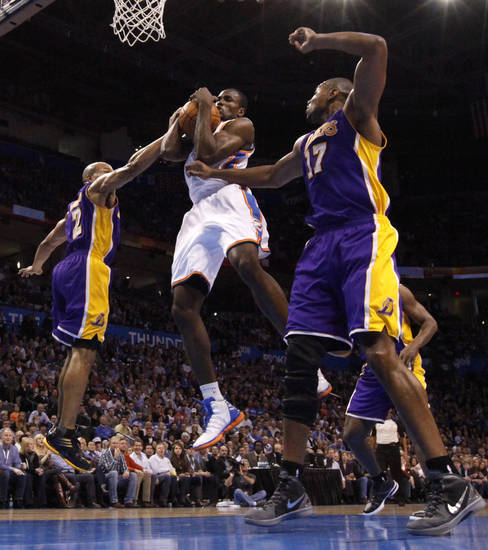 Oklahoma City's Serge Ibaka (9) grabs a rebound between Los Angeles' Derek Fisher (2) and Andrew Bynum (17) during an NBA basketball game between the Oklahoma City Thunder and the Los Angeles Lakers at Chesapeake Energy Arena in Oklahoma City, Thursday, Feb. 23, 2012. Photo by Bryan Terry, The Oklahoman
