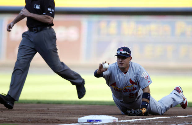 St. Louis Cardinals first baseman Allen Craig, right, tosses an Atlanta Braves' Martin Prado-hit ball to Cardinals starting pitcher Kyle Lohse for an out during the National League wild card playoff baseball game on Friday, Oct. 5, 2012, in Atlanta. (AP Photo/John Bazemore)