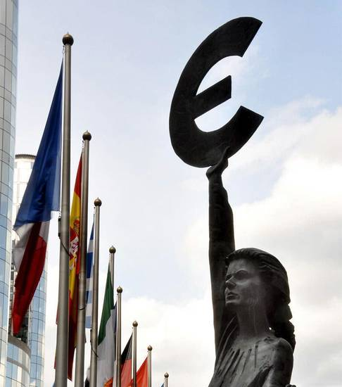 This statue, just outside the European Parliament in Brussels, holds the symbol of the euro � Europe�s common currency. Photo by Cameron Hewitt