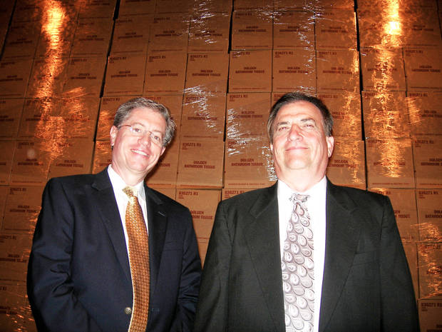 Above: Keith R. Schroeder, chief financial officer, and Robert A. Snyder, president and CEO, stand in front of boxes of bathroom tissue at Orchids Paper Products.