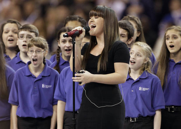 Kelly Clarkson sings the national anthem before the NFL Super Bowl XLVI football game between the New York Giants and the New England Patriots, Sunday, Feb. 5, 2012, in Indianapolis. (AP Photo/Chris O'Meara)