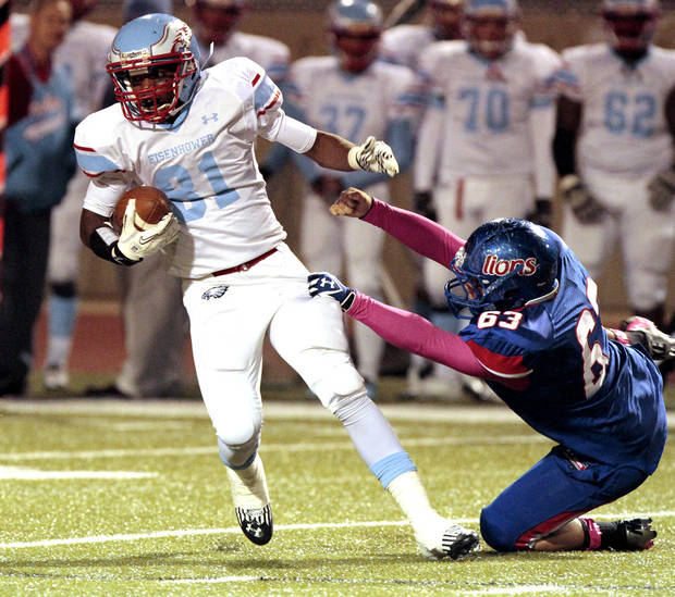 Eisenhower's Andy Green (81) avoids the tackle of Josh Robison (63) as the Moore Lions play the Lawton Eisenhower Eagles in a high school football game on Friday, Oct. 5, 2012, in Moore, Okla.  Photo by Steve Sisney, The Oklahoman