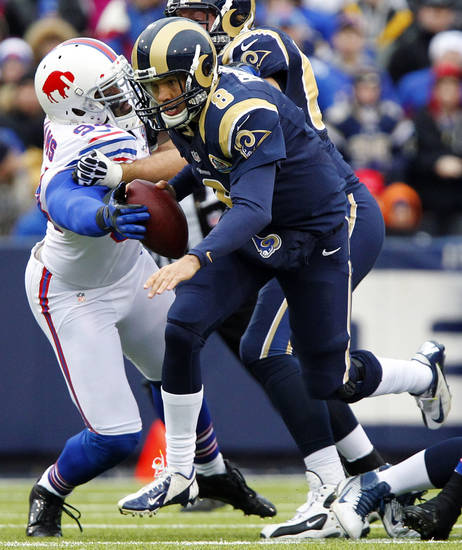 Buffalo Bills defensive end Mario Williams, left, forces a fumble on St. Louis Rams quarterback Sam Bradford during the first half of an NFL football game, Sunday, Dec. 9, 2012, in Orchard Park, N.Y. Bradford recovered the ball on the play. (AP Photo/Bill Wippert)
