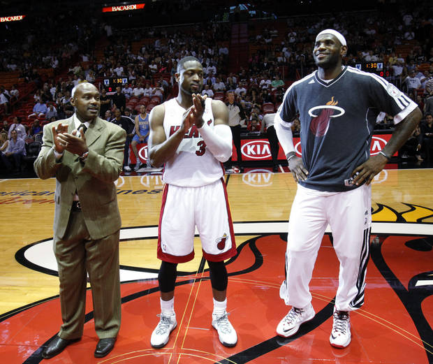 Miami Heat forward LeBron James, right, smiles as he, former Heat player Tim Hardaway, right, and guard Dwyane Wade, center, look on as the Heat unveiled a banner to commemorate James' participation on the gold-medal winning U.S. men's basketball team at this summer's London Olympics, during a ceremony before the start of an NBA basketball game against the Denver Nuggets, Saturday, Nov. 3, 2012 in Miami. His banner sways next to those honoring previous Heat players who were gold-medal winners: Dwyane Wade (2008), Alonzo Mourning (2000) and Tim Hardaway (2000). (AP Photo/Wilfredo Lee)