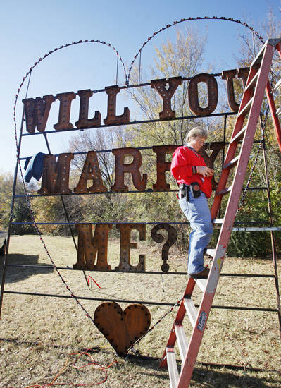 Right: Yukon city worker Julia Puckett strings Christmas lights on the �Will you marry me?� sign at Chisholm Trail Park.  Photo by Paul B. Southerland, The Oklahoman