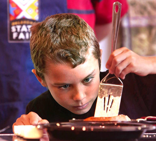 James McAffrey, 9, carefully places a spatula around the edges of a pancake as he prepares to flip his custom creation of Boston Cream Pie Pancakes while competing in the Shawnee Mills&#039;  Kids&#039; Pancakes, Flapjacks and Griddle Cakes Contest at the Oklahoma State Fair on Saturday, Sep. 22, 2012. The event was held in the Creative Arts Building. McAffrey of Oklahoma City, is home-schooled.  Photo by Jim Beckel, The Oklahoman.