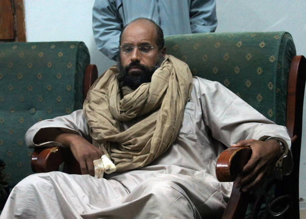 FILE - In this Saturday, Nov. 19, 2011 file photo, Seif al-Islam is seen after his capture in the custody of revolutionary fighters in Zintan, Libya. Libya's official news agency says the imprisoned son of slain dictator Muammar Gaddafi has made his first appearance in a local court on charges of harming state security, attempting to escape prison and insulting the nation's new flag. (AP Photo/Ammar El-Darwish, File)