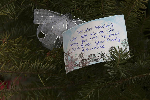 A note is left at one of the makeshift memorials for the Sandy Hook Elementary School shooting victims, Monday, Dec. 17, 2012 in Newtown, Conn. Authorities say gunman Adam Lanza killed his mother at their home on Friday and then opened fire inside the Sandy Hook Elementary School in Newtown, killing 26 people, including 20 children, before taking his own life. (AP Photo/Mary Altaffer) ORG XMIT: CTMA117