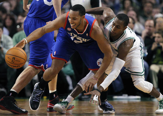 Philadelphia 76ers' Evan Turner (12) and Boston Celtics' Rajon Rondo, right, scramble for a loose ball in the second quarter of an NBA basketball game in Boston, Friday, Nov. 9, 2012. (AP Photo/Michael Dwyer)