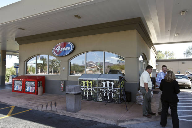 Owner Eric Seitz, back right, stands out in front of his store, at a 4 Sons Food Store, as people gether where one of the winning tickets in the $579.9 million Powerball jackpot was purchased, Nov. 29, 2012, in Fountain Hills, Ariz.(AP Photo/Ross D. Franklin)
