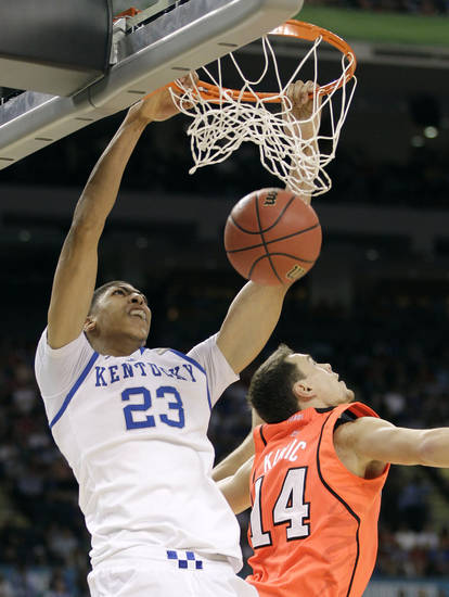  Kentucky&#039;s Anthony Davis (23) dunks the ball over Louisville&#039;s Kyle Kuric during the first half of an NCAA Final Four semifinal college basketball tournament game Saturday, March 31, 2012, in New Orleans. (AP Photo/Mark Humphrey)  