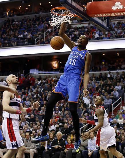 Oklahoma City Thunder forward Kevin Durant (35) dunks as Washington Wizards center Marcin Gortat, left, from Poland, and guard Bradley Beal, right, watch in the first half of an NBA basketball game on Saturday, Feb. 1, 2014, in Washington. (AP)