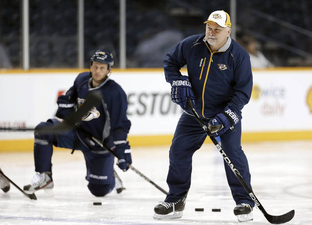 Nashville Predators head coach Barry Trotz, right, passes a puck at NHL hockey training camp on Wednesday, Jan. 16, 2013, in Nashville, Tenn. The shortened, 48-game season begins Saturday, January 19. Forward Rich Clune, left, looks on. (AP Photo/Mark Humphrey)