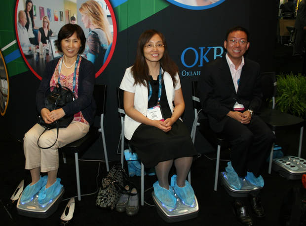 Visitors from China take advantage of the ever-popular foot massagers at the Oklahoma booth. PHOTO BY JIM STAFFORD, FOR THE OKLAHOMAN