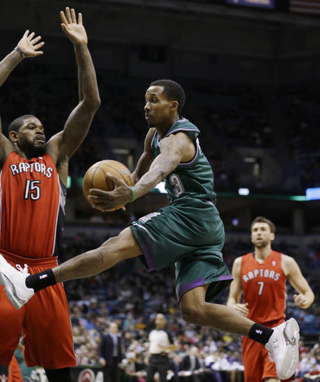 Milwaukee Bucks' Brandon Jennings(13) passes around Toronto Raptors' Amir Johnson (15) during the second half of an NBA basketball game Saturday, March 2, 2013, in Milwaukee. (AP Photo/Jeffrey Phelps)