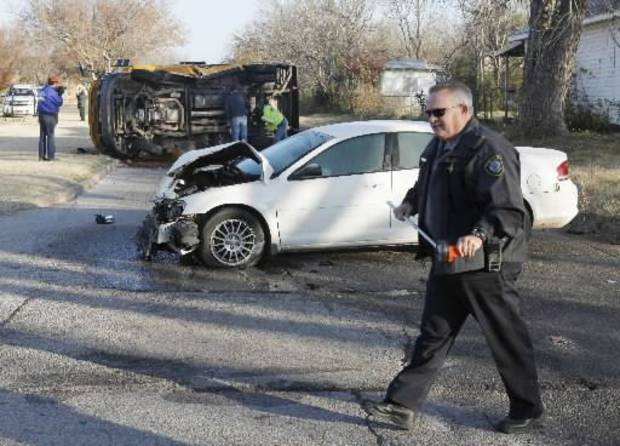 Emergency workers investigate an accident involving a school bus and an automobile at the intersection of NW 89th and Classen in Oklahoma City, OK, Tuesday, November 27, 2012, By Paul Hellstern, The Oklahoman