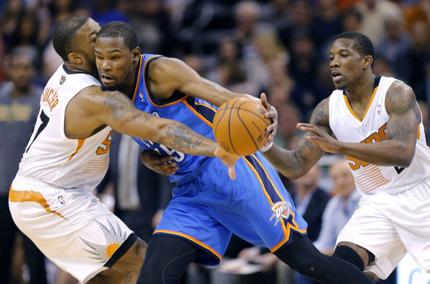 Oklahoma City Thunder forward Kevin Durant, center, collides with Phoenix Suns forward P.J. Tucker (17) during the first half of an NBA basketball game as Suns' Eric Bledsoe watches on Sunday, April 6, 2014, in Phoenix. The Suns won 122-115. (AP Photo/Matt York)