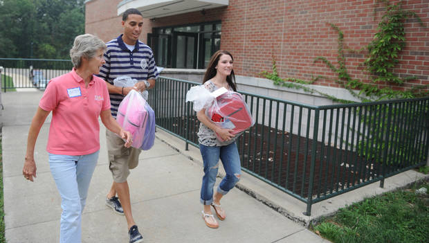 Eastside Community Ministry board member Betsy Thomas, Kevin Martin and his wife Jill Martin help deliver backpacks in his hometown of Zanesville, Ohio in this August 2012 file photo. Eastside Community Ministry hosted its annual Tools for Schools giveaway, passing out 753 backpacks stuffed with school supplies. Photo courtesy Zanesville Times Recorder.