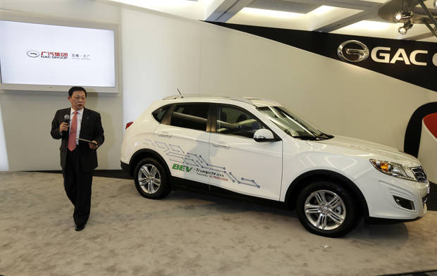 Guangzhou Automobile Group Vice President Xiangdong Huang, stands next to the automaker's Trumpchi GS5 concept, a pure electric vehicle, during the North American International Auto Show in Detroit, Tuesday, Jan. 15, 2013. (AP Photo/Carlos Osorio)