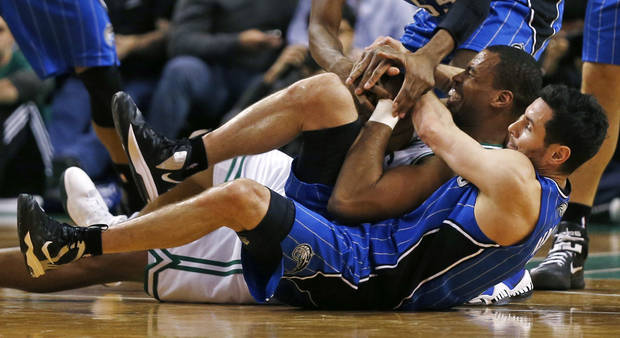 Orlando Magic guard J.J. Redick, bottom, and Boston Celtics center Jason Collins (98) hit the floor as they battle for the ball during the second half of an NBA basketball game in Boston, Friday, Feb. 1, 2013. The Celtics won 97-84. (AP Photo/Charles Krupa)