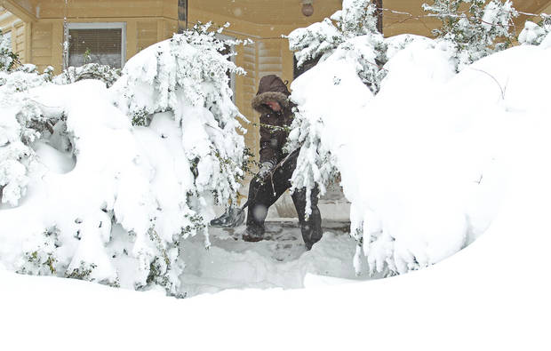 Frank Perry shovels snow from his front porch as the weight of the snow causes the bushes to sag, Saturday, Feb. 9, 2013, in Providence, R.I. A howling storm across the Northeast left the New York-to-Boston corridor shrouded in 1 to 3 feet of snow Saturday, stranding motorists on highways overnight and piling up drifts so high that some homeowners couldn't get their doors open. More than 650,000 homes and businesses were left without electricity.  (AP Photo/Stew Milne)