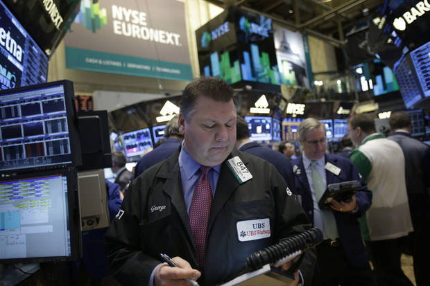 In this Tuesday, Feb. 19, 2013 photo, traders work on the floor at the New York Stock Exchange in New York. Stock futures are moving slightly lower Wednesday, Feb. 20, with the U.S. expected to report that homebuilding slowed during the first month of the year. (AP Photo/Seth Wenig)
