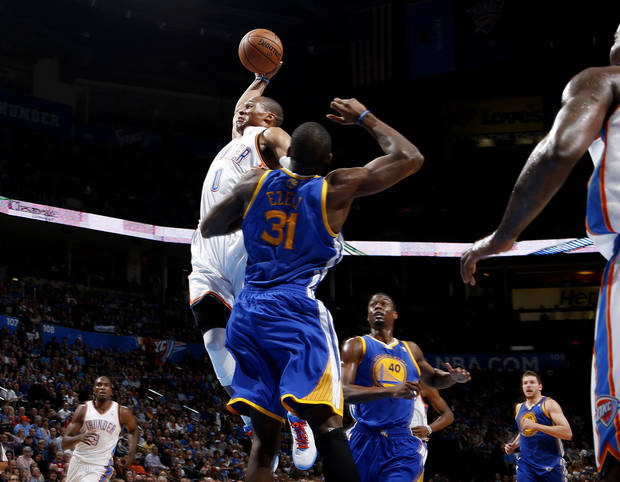 Oklahoma City's Russell Westbrook (0) goes to the basket beside Golden State's Festus Ezeli (31) during an NBA basketball game between the Oklahoma City Thunder and the Golden State Warriors at Chesapeake Energy Arena in Oklahoma City, Wednesday, Feb. 6, 2013. Photo by Bryan Terry, The Oklahoman