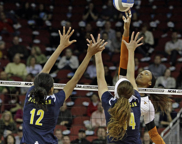 Texas outside hitter Bailey Webster uses her finger tips to avoid the double-block attempt by Michigan's Krystalyn Goode (12) and Claire McElheny (14) during the national semifinals of the NCAA college women's volleyball tournament semifinal in Louisville, Ky., Thursday, Dec. 13, 2012.  (AP Photo/Garry Jones)