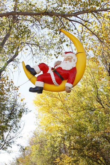 Santa reclines in a sliver of moon hanging from a tree at Chisholm Trail Park in Yukon.