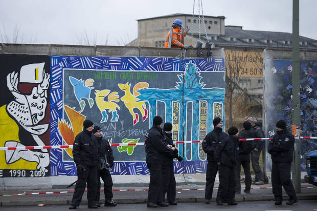 German police officers protect a part of the former Berlin Wall and a construction worker who fixed a part of the wall at a crane in Berlin, Germany, Friday, March 1, 2013. Construction crews stopped work Friday on removing a small section from one of the few remaining stretches of the Berlin Wall to make way for a condo project after hundreds of protesters blocked their path. (AP Photo/Markus Schreiber)