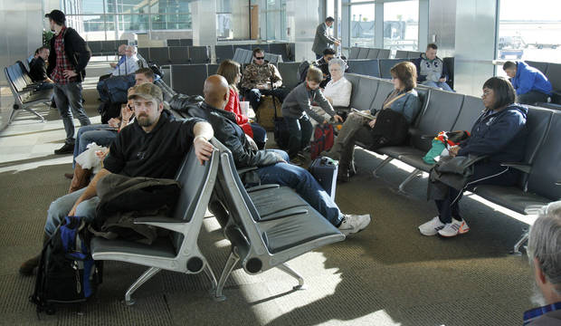 Travelers wait for their flights at Will Rogers World Airport on Tuesday. Photo by PAUL HELLSTERN, The Oklahoman
