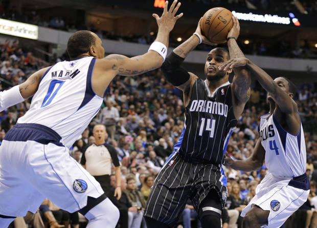 Dallas Mavericks' Shawn Marion (0) and Darren Collison (4) defend against a drive to the basket by Orlando Magic's Jameer Nelson (14) during the first half of an NBA basketball game Wednesday, Feb. 20, 2013, in Dallas. (AP Photo/Tony Gutierrez)