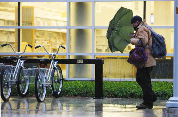 A pedestrian fights the wind and rain with an umbrella while walking past the Ronald J. Norick Downtown Library on Park Ave. in Oklahoma City Wednesday, April 10, 2013. Photo by Paul B. Southerland, The Oklahoman