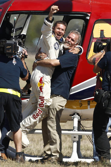 Felix Baumgartner, left, of Austria, celebrates with Art Thompson, Technical Project Director, after successfully jumping from a space capsule lifted by a helium balloon at a height of just over 128,000 feet above the Earth&#039;s surface, Sunday, Oct. 14, 2012, in Roswell, N.M.  Baumgartner landed in the eastern New Mexico desert minutes after jumping from his capsule 28,000 feet (8,534 meters), or 24 miles (38.6-kilometer), above Earth (AP Photo/Ross D. Franklin) ORG XMIT: NMRF116
