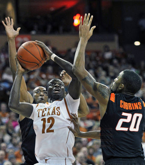 Texas guard Myck Kabongo (12) goes up for a shot against Oklahoma State guard Le'Bryan Nash, left, and Michael Cobbins (20) during the second half of an NCAA college basketball game Saturday, Jan. 7, 2012, in Austin, Texas. Kabongo led Texas with 15 points as Texas won 58-49. (AP Photo/Michael Thomas) ORG XMIT: TXMT108