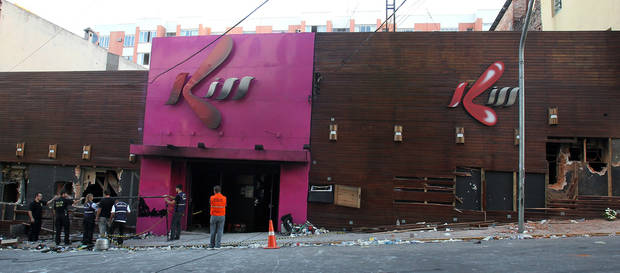 Police investigators inspect the entrance of the Kiss nightclub in Santa Maria city, Rio Grande do Sul state, Brazil, Sunday, Jan. 27, 2013. Flames raced through the crowded nightclub in southern Brazil early Sunday, killing more than 230 people as panicked partygoers gasped for breath in the smoke-filled air, stampeding toward a single exit partially blocked by those already dead. (AP Photo/Nabor Goulart)