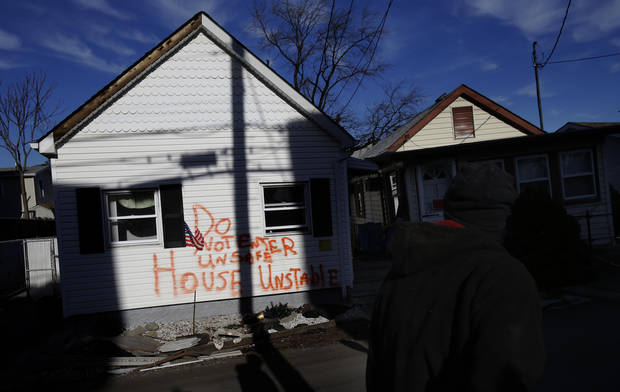 A man walks past homes severely damaged by Superstorm Sandy in Staten Island, New York, Thursday, Jan. 10, 2013.  (AP Photo/Seth Wenig)
