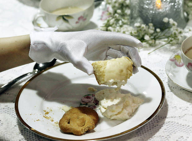 Left: McClane Wylie, 8, lifts a piece of finger food from her plate during the Edmond Historical Society and Museum Victorian tea. Many of the 48 girls were dressed in Victorian-style clothing, hats and gloves as they learned manners.
