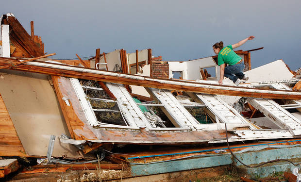 Rebecca Apel, 15, climbs on top of a toppled wall on the west side of her family's home in search of her pet birds. She located the cage, but only one of her four birds survived after a tornado came through the area Tuesday afternoon,  May 24, 2011,   Photo by Jim Beckel, The Oklahoman