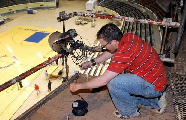 Oklahoman staff photographer Chris Landsberger checks a strobe light in the catwalk at State Fair Arena in preparation for the state high school basketball championships, in Oklahoma City, Monday, March 2, 2009. BY NATE BILLINGS, THE OKLAHOMAN