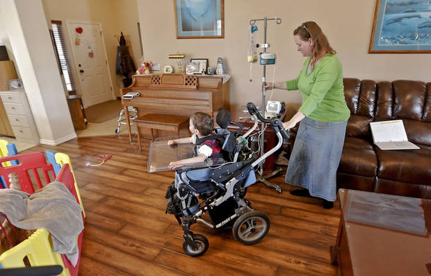 Ashley Zeno moves with her son Joey while pulling along his feeding tube unit at their home on Monday, March 4, 2013, in Mustang, Okla. Joey has Cri du Chat syndrome which is a condition that is similar to autism, but requires around the clock medical supervision. Zeno, a single mom, is a nurse as well as Joey's in home nurse. Recent proposals by The Oklahoma Health Care Authority want to eliminate the ability of family members serving as in-home nurses, and being reimbursed for the care they provide. For Zeno, this means she would need to find two dependable in-home nurses, and a job outside the home that would let her take off for the multiple doctor appointments Joey requires each week.